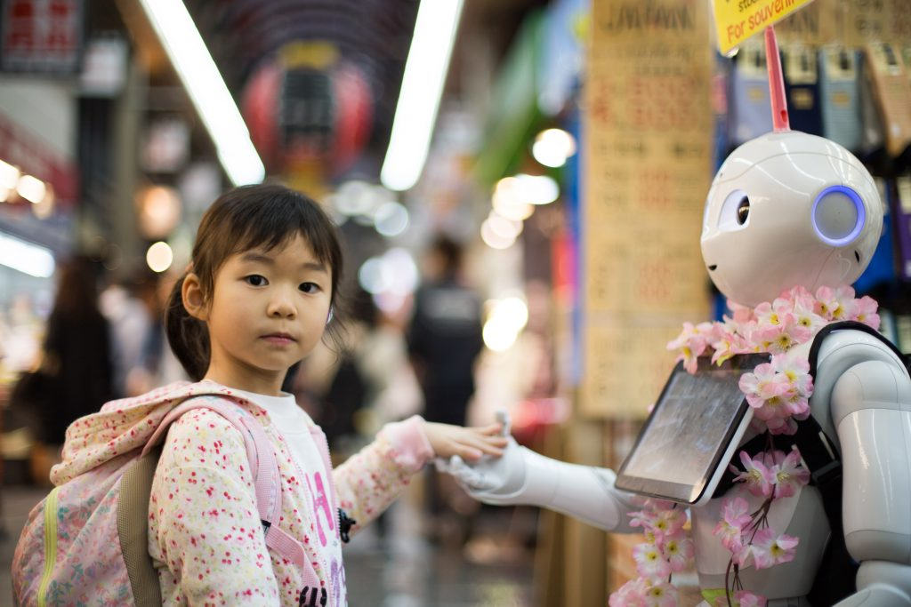 Image of a child interacting with a robot, signifies the role of Machine Learning and is futuristic